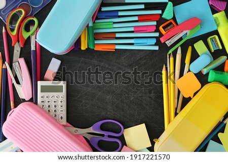 Frame of different stationery on blackboard, flat lay with space for text. Back to school Royalty-Free Stock Photo #1917221570