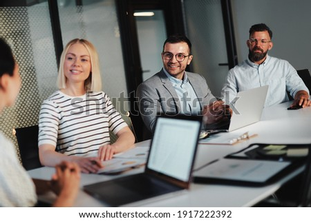 Group of smiling businesspeople talking together during a meeting around a table in the boardroom of a modern office Royalty-Free Stock Photo #1917222392