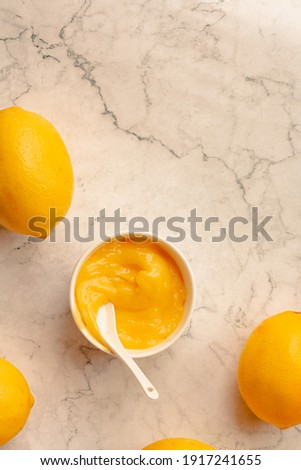Homemade tangy lemon curd decorated with fresh fruit on marble background.Top view. Copy space for text. Royalty-Free Stock Photo #1917241655