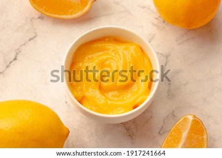 Delicious homemade tangy lemon curd decorated with fresh fruit on marble background.Top view. Royalty-Free Stock Photo #1917241664