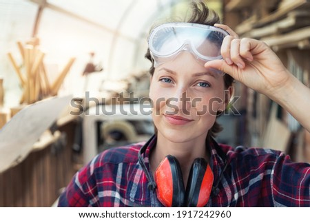 Young beautiful handy professional happy female strong carpenter portrait wearing protective goggles working in carpentry diy workshop against wood. Confident engineer. Women male hobby at workbench Royalty-Free Stock Photo #1917242960