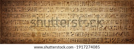 Old Egyptian hieroglyphs on an ancient background. Wide historical background. Ancient Egyptian hieroglyphs as a symbol of the history of the Earth.  Royalty-Free Stock Photo #1917274085