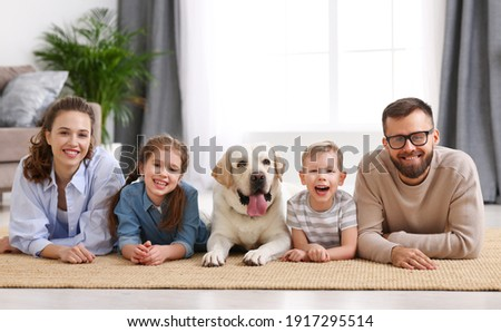 Smiling mother and father with little kids and adorable purebred Labrador retriever dog lying on floor and looking at camera while spending time together at home Royalty-Free Stock Photo #1917295514