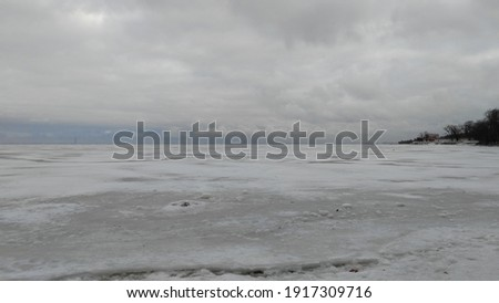 Distant horizon of gray ice and sky. Winter coast of the Gulf of Fink. The water in the bay froze over the ice and the snow on it. Above are gray-white clouds. Everything merges into shades of gray. Royalty-Free Stock Photo #1917309716