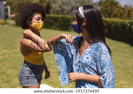 Two diverse female friends wearing face masks bumping elbows at a pool party. Health and hygiene precautions while hanging out and relaxing outdoors in summer during coronavirus covid 19 pandemic. Royalty-Free Stock Photo #1917376409