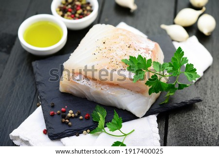 Cod fillet with spices on a black background
