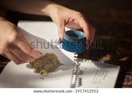 breaking up dried cannabis flower buds in an aluminum grinder releasing kief psychoactive THC pollen to mix and roll into a hemp Delta 8 legal pre-rolled retail joint for personal recreational use