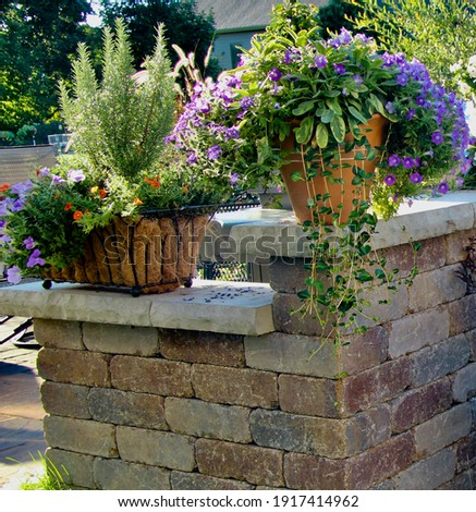 horizontal picture of a retaining wall with capstone ledges wide enough to hold terra cotta containers of herbs and flowers