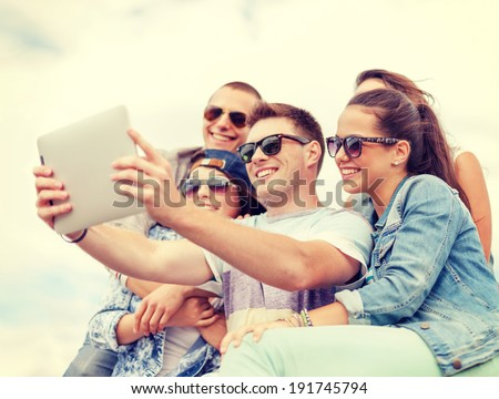 summer holidays, teenage and technology concept - group of smiling teenagers in sunglasses taking selfie with tablet pc