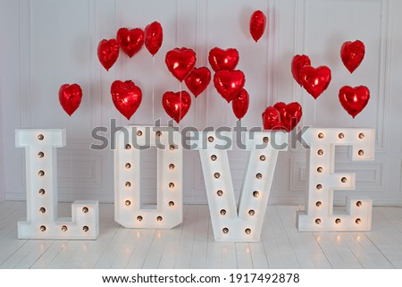 Love big letters with led retro bulbs glowing. Word LOVE illuminated with a big letters. Inscription is love. Glowing large letters. Wedding decor. Red heart balloons. air balls in shape of red heart