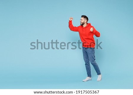 Full length of young caucasian happy bearded overjoyed excited man 20s in casual red orange hoodie do winner gesture clenching fist celebrate look aside isolated on blue background studio portrait Royalty-Free Stock Photo #1917505367