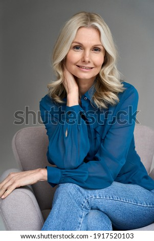 Sophisticated smiling elegant beautiful 50s attractive middle aged smiling woman model sitting in chair looking at camera at home. Vertical portrait of gorgeous confident mature older blond hair lady. Royalty-Free Stock Photo #1917520103