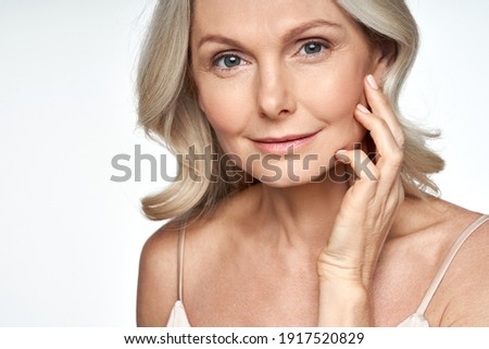 50s mid aged woman touching face skin looking at camera. Attractive mature old woman looking at camera isolated on white background advertising dry skin care treatment anti age skincare. Close up view Royalty-Free Stock Photo #1917520829