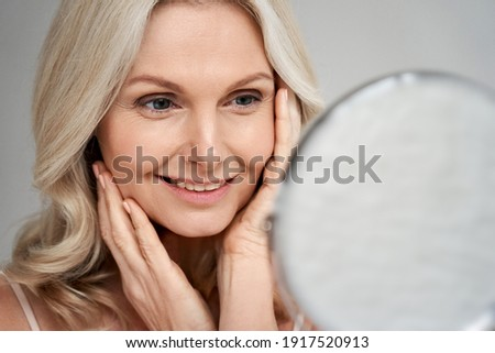 Happy 50s middle aged woman model touching face skin looking in mirror. Smiling mature older lady pampering, enjoying healthy skin care, aging beauty, skincare treatment cosmetic products concept. Royalty-Free Stock Photo #1917520913