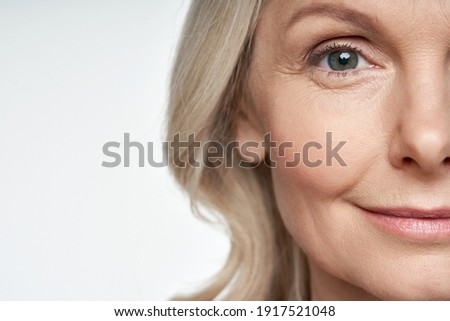 50s middle aged old woman looking at camera isolated on white background advertising dry skin care treatment anti age skincare beauty, plastic surgery, cosmetology procedures. Close up half face view Royalty-Free Stock Photo #1917521048
