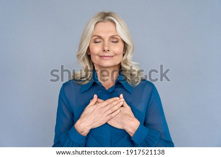 Happy mindful thankful middle aged old woman holding hands on chest meditating with eyes closed isolated on grey background feeling no stress, gratitude, mental health balance, peace of mind concept. Royalty-Free Stock Photo #1917521138
