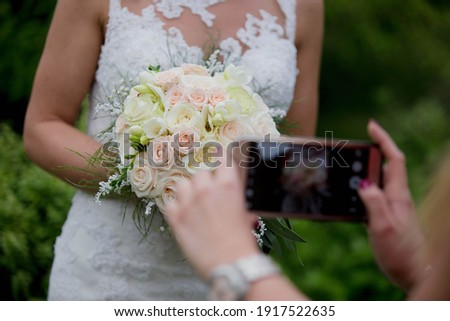 A closeup of a person taking a picture of the bride holding a bouquet of flowers in a garden