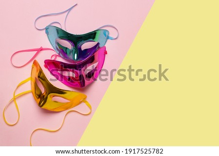 Multicolored carnival mask on yellow-pink background. Top view. Banner