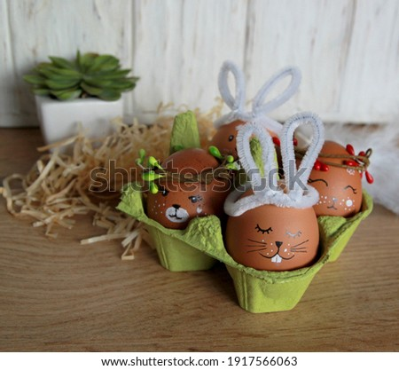 Cute do-it-yourself Easter eggs decor, hand-drawn drawings of an Easter bunny, animal faces in wreaths of spring twigs, green egg stand on a wooden background with feathers and straw, Easter festive d