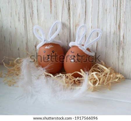 A pair of do-it-yourself easter bunnies, cute bunny faces with white ears on a wooden natural background, delicate decor for the holiday