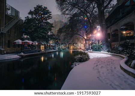Snow Day at the San Antonio Riverwalk in Texas. Snowy winter weather. A rare snow storm in Texas came over the River Walk in downtown San Antonio. Blizzard, hail, icy weather and Christmas Lights Royalty-Free Stock Photo #1917593027