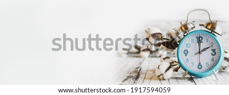 Set your clocks back with this banner of a clock and cotton over a white wooden table. Daylight saving time concept. Selective focus with blurred background.