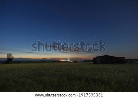 The Neowise comet in the night sky over meadow with wooden barn in morning twilight before sunrise in the Eifel, Germany Royalty-Free Stock Photo #1917595331