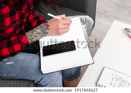 hands of a girl with a tattoo, fills a notebook, phone