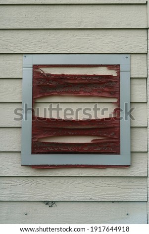 Distressed red square on the side of a building that has been condemned.                                 Royalty-Free Stock Photo #1917644918
