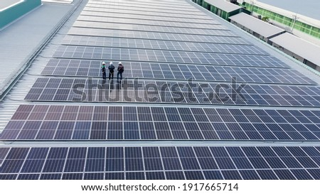 Solar panels installed on a roof of a large industrial building or a warehouse. Industrial buildings in the background. Horizontal photo. Royalty-Free Stock Photo #1917665714