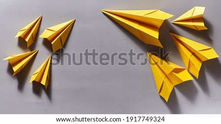 yellow paper airplanes on a gray background. close-up, copy space Royalty-Free Stock Photo #1917749324