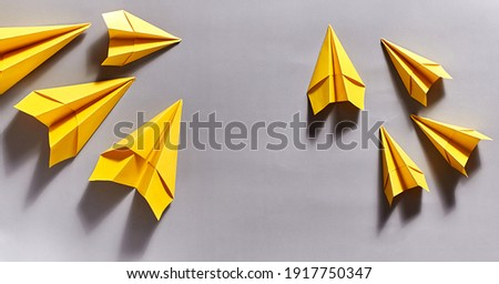 yellow paper airplanes on a gray background. close-up, copy space Royalty-Free Stock Photo #1917750347