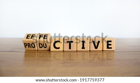 Effective and productive symbol. Turned wooden cubes, changed the word 'productive' to 'effective'. Beautiful wooden table, white background, copy space. Business, effective and productive concept. Royalty-Free Stock Photo #1917759377
