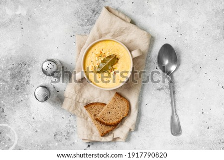 The cream of chicken soup. Puree soup chicken, carrot and onion soup with cream. Chicken soup in a bowl on the light gray kitchen table. Top view Royalty-Free Stock Photo #1917790820