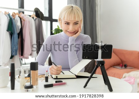 A beautiful pretty girl at home at the table is studying by video conference in the zoom on the phone. A young beauty fashion blogger takes off her vlog and smiles.