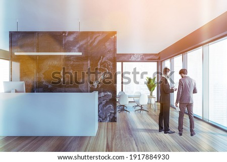 Two colleagues discussing clients business case before the meeting in modern panoramic office in downtown. reception area and fulllengthwindows. Lens flare Royalty-Free Stock Photo #1917884930