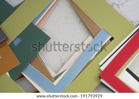 Multiple colored picture mat boards hanging on a wall.