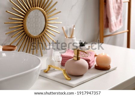 Tray with different toiletries, burning candle and towels near vessel sink in bathroom Royalty-Free Stock Photo #1917947357