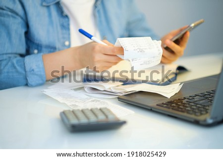 woman using a pen writing on bank account book while holding the bills to calculate in living room at home. Expenses, account, taxes, home budget concept Royalty-Free Stock Photo #1918025429