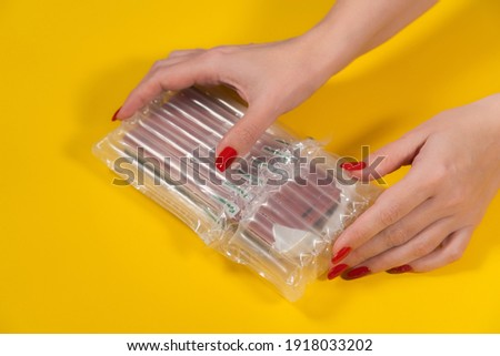 Closeup view color stock photography of female hands unpacking her online order wrapped in protective plastic air pack for shipping safely fragile goods