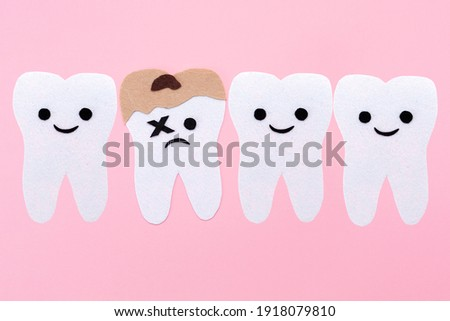 A row of teeth with cartoon faces carved out of felt. One tooth is affected by caries. Pink background. Copy space. The concept of stomatology and oral hygiene.