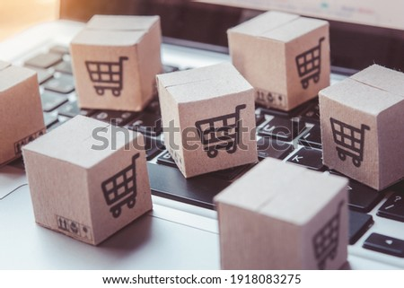 Shopping online. Cardboard box with a shopping cart logo on laptop keyboard. Shopping service on The online web. offers home delivery Royalty-Free Stock Photo #1918083275