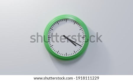 Glossy green clock on a white wall at twenty past four. Time is 04:20 or 16:20 Royalty-Free Stock Photo #1918111229