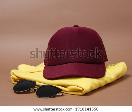 Blank baseball caps are used for design mockups. The hat on the side of an old camera and sunglasses. Plain hat isolated on brown background. Take a picture of a hat ready to be displayed. Mockup hat.