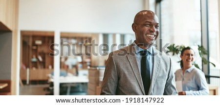 Laughing African American businessman walking in an office holding paperwork after a meeting with colleagues  Royalty-Free Stock Photo #1918147922