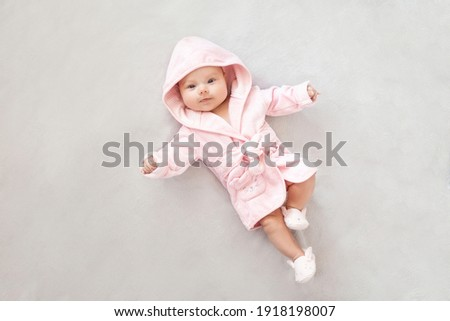 Baby girl in a Terry robe and diaper after bathing. Kid in a hood. Cute happy laughing baby girl in pink soft robe after bath. Baby in a clean and dry towel.baby hygiene, health and skin care.  Royalty-Free Stock Photo #1918198007