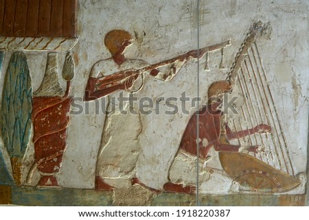 A wall painted scene with a harpist and other musician from the tomb of Benia (TT 343) in Thebes - Luxor, Egypt Royalty-Free Stock Photo #1918220387