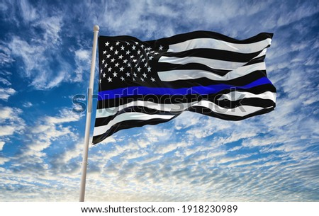 Thin Blue Line. Black Flag of USA with Police Blue Line waving in the wind on flagpole against the sky with clouds on sunny day Royalty-Free Stock Photo #1918230989