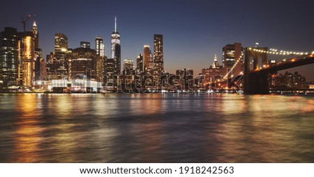Manhattan skyline and Brooklyn Bridge reflected in water at dusk, New York City, USA.
