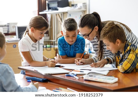 Female teacher helps school kids to finish they lesson.They sitting all together at one desk.  Royalty-Free Stock Photo #1918252379